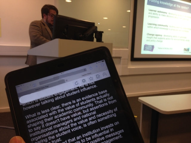 Someone reading text off an ipad. The speaker can be seen in the background.